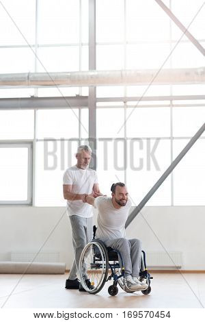 Supporting disabled people. Skillful cheerful aged physical therapist helping the disabled man and providing a rehabilitation session while expressing positivity