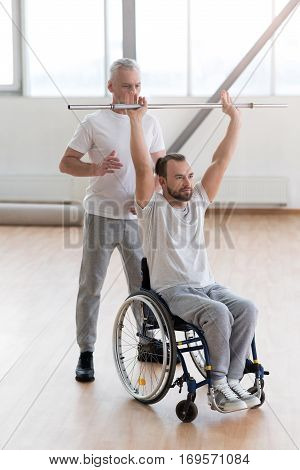 The process of rehabilitation. Concentrated muscular aged coach helping the disabled patient and providing an alternative therapy session while working with equipment and expressing concentration