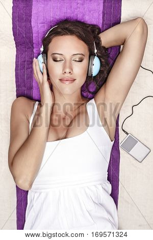 Young woman listening to music through MP3 player using headphones while lying on picnic blanket