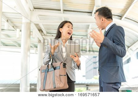 Angry Asian business people at heated dispute or argument and negotiation process breaks down. Businesswoman holding digital tablet and shouting to boss. Businessman misunderstanding with colleagues.