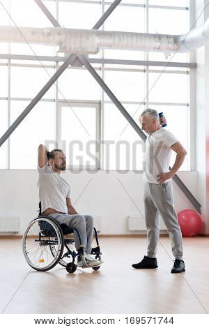 On my way to recovery. Athletic skilled aged coach teaching the disabled man in the wheelchair and providing physical therapy session in the gym while holding dumbbells and expressing concentration