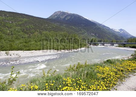 The view of Skagway River in Skagway town with AB Mountain in a background.