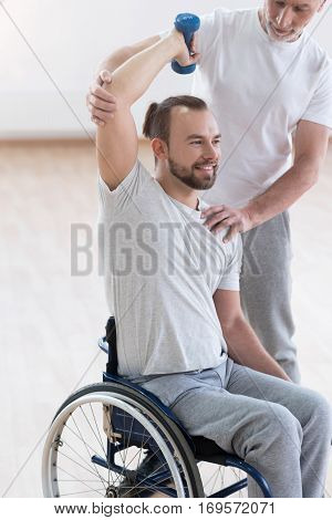 Beginning the new life. Skilled happy cheerful disabled man holding the dumbbell and having the lesson with his coach while having the physical therapy session in the gym