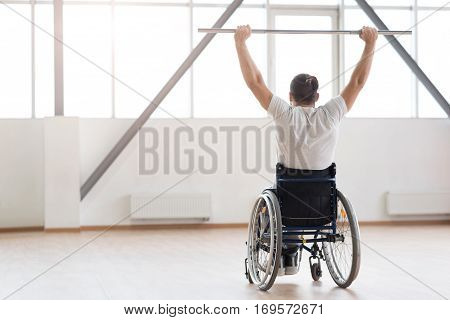 Becoming stronger every day. Athletic muscular young invalid sitting in the wheelchair in the gym and looking at the window while exercising and holding the metal barbell
