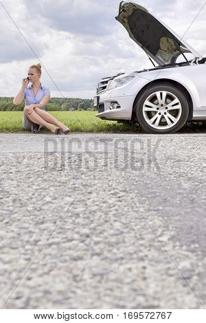Full length of mid adult businesswoman using cell phone while sitting beside broken down car at countryside