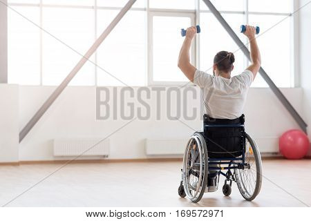 Sport as a lifestyle. Skilled powerful hardworking invalid sitting in the wheelchair in the gym and looking at the window while exercising and holding the dumbbells