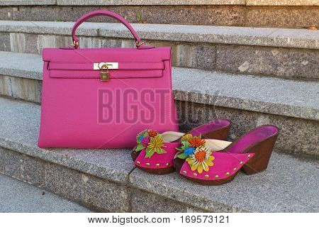 Bright neon pink pair of women's mule shoes with big handbag on a marble stairs, shoes are decorated by floral decor