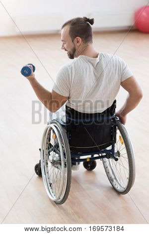 Improving myself. Muscular cheerful purposeful invalid sitting in the wheelchair in the gym and looking at his arm while exercising and holding the dumbbell