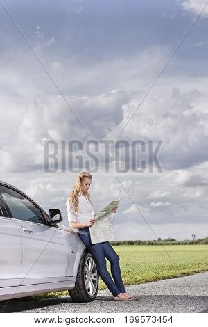 Full length of mid adult woman leaning on car while reading map at countryside