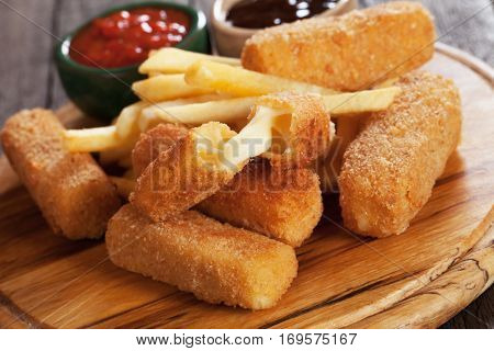 Breaded mozzarella cheese sticks with french fries and tomato sauce