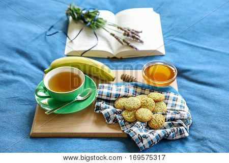 Breakfast served in bed - green tea lemon cookies apple banana honey on a wooden board on background of blue denim bed linens open book and bunch of lavender. Tasty breakfast in bed concept.