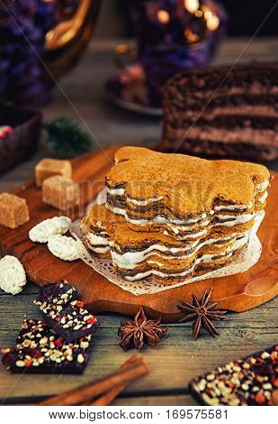 honey layer cake piece with chocolate, nuts, anise and cinnamon with tea lying on the table