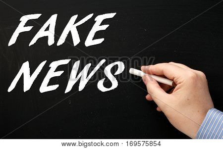 Male hand writing the words Fake News in white text on a blackboard as a reminder to be aware of hoaxes and disinformation for propaganda uses