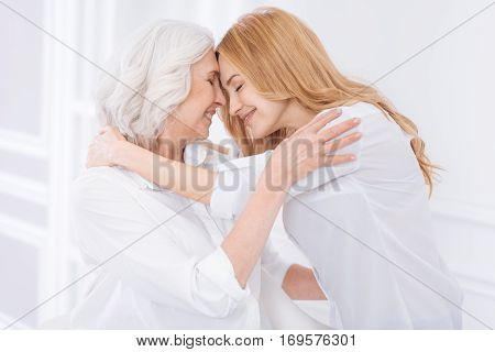 My dear. Delighetd loving adult woman and her mother embracing and expressing love while resting together at home