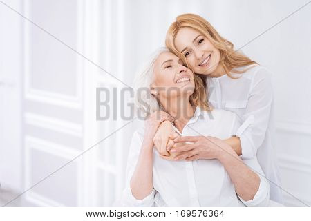 Warm relations. Ceerful delighted loving mother and her adult daughter resting at home and expressing love while embracing