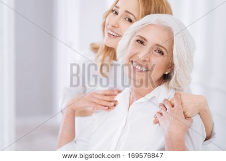 True emotions. Cheerful delighted aged woman smiling and feeling delighted while embracing with her daughter
