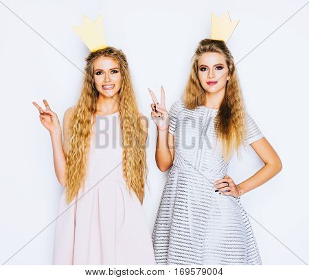 Two beautiful young women celebrate party show victory sign on white background. Best friends wearing stylish evening dress, gold crown on head . Princess and Queen.