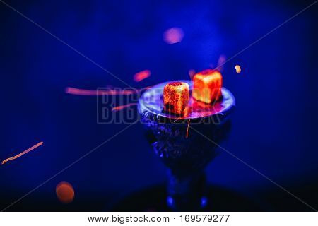 Hot coals on the bowl of the hookah with sparks for a traditional Eastern relaxation and enjoyment on a blue blurred background