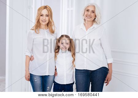 Full of gladness. ositive content smiling little girl and her mother and grandmother embracign and expressing joy at home