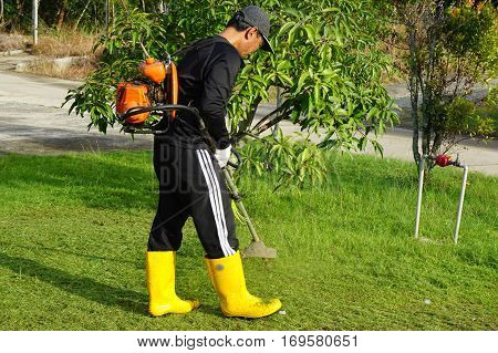 Labuan,Malaysia-Feb 5,2017:The worker of a garden cuts off a grass in Labuan,Malaysia on 5th Feb 2017.