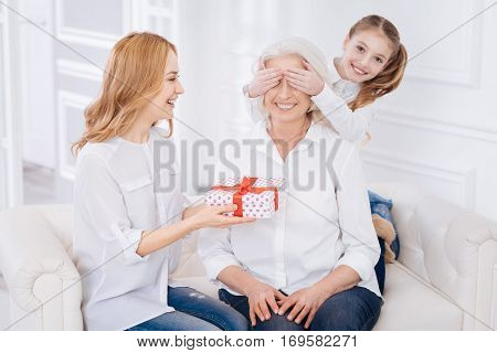 Ready to open. Positive content aged woman sitting on the couch while her loving family holding present and congratulating her