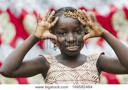 Young african girl with traditional accessories in hair doing gestures and looking at camera