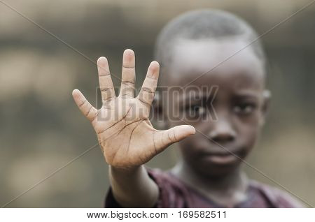 Little african boy showing palm as stop sign for racism and war