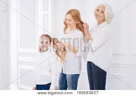Love and care. Positive delighted female family members expressing gladness and making hairstyles for each other while resting together at home