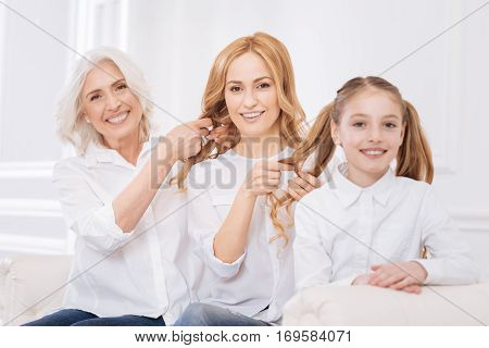 Loving relationships. Cheerful content female family members sitting on the couch and making hairstyle for each other while resting at home