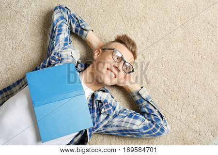 Handsome young man with book lying on carpet