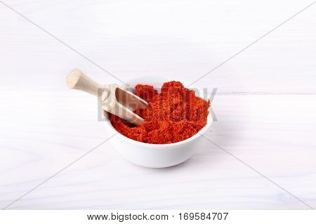 Sweet paprika powder in bowl on white.