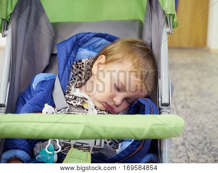 Little baby sleeping in a stroller .