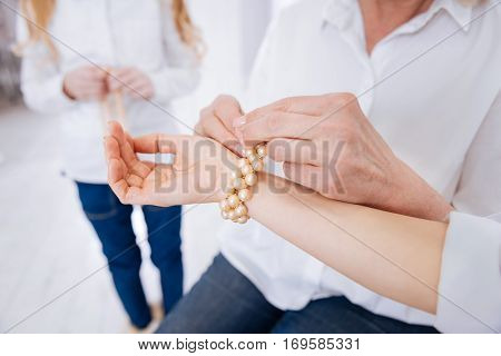 I need your help. Pleasant aged woman helping to wear bracelet for her adult daughter