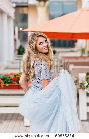 Beautiful blonde girl walking on terrace background. She holds long blue tulle skirt in hand and smiling to camera