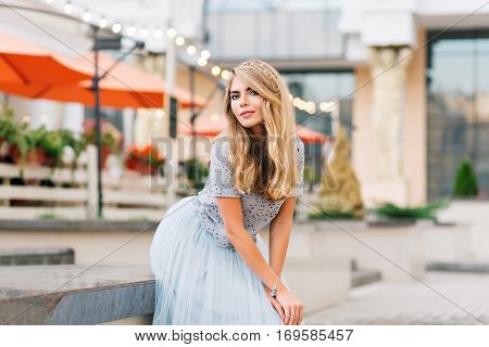Attractive girl girl with long blonde hair in blue tulle skirt leaning on concrete bench on street. She is looking to camera