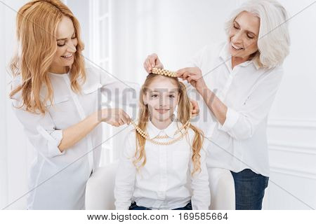 Little princess. Cheerful pretty little girl smiling and resting with her family while wearing accessories