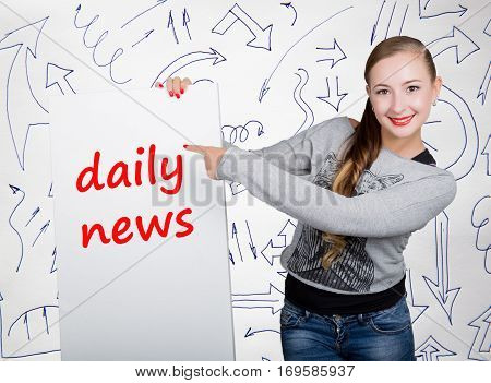 Young woman holding whiteboard with writing word: daily news. Technology, internet, business and marketing