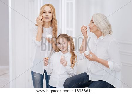 Make it perfect. Cheerful delighted female family members using beauty cream and smiling while resting together at home