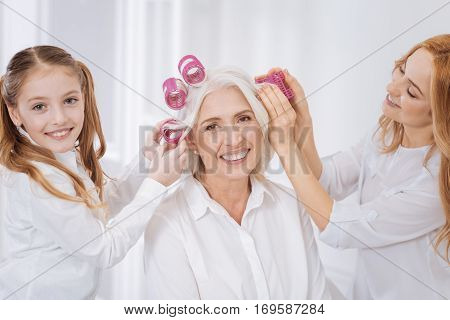 Make it curly. Cheerful delighted woman and her daughetr helping to curl hair of smiling loving grandmother while resting at home