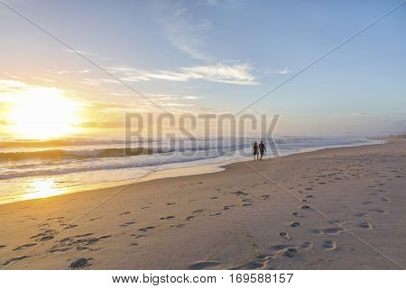 People walking on a beach into the distance, as the sunrises over the ocean.