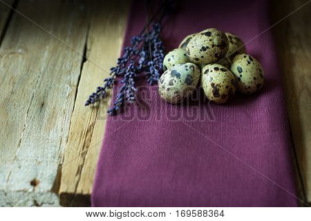 Quail eggs and lavender twigs on a lilac linen cloth on barn wood background, Easter, rustic vintage style, kinfolk, simplicity, close up