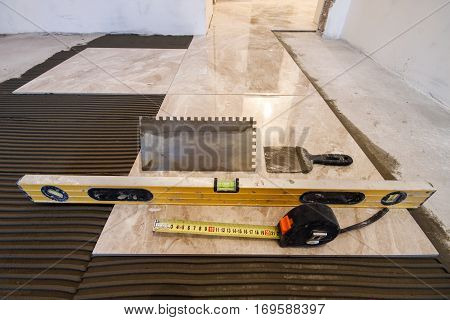 Ceramic tiles and tools for tiler. Floor tiles installation. Home improvement renovation - ceramic tile floor adhesive trowel with mortar level measuring tape