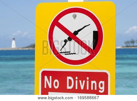 The warning sign prohibiting diving standing on Nassau city beach (Bahamas).