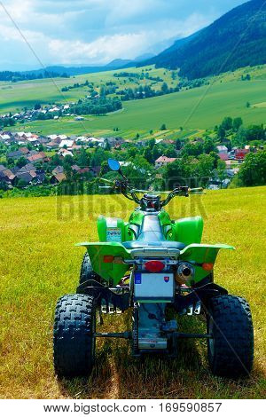 Green Quad in landscape with village in the background