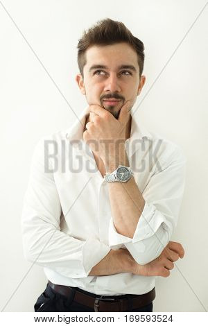 Thinking handsome man think about something standing against white background. Portrait of handsome young thoughtful man isolated over white background.Young man doubting isolated over gray background