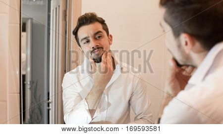 Man take care about his skin. Cheerful beaded guy caring of his skin. Handsome man look in mirror in bathroom in early morning