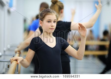 Girl in black leotard work out pas at ballet class, other girls out of focus