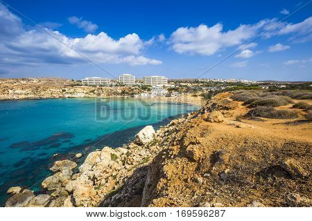 Ghajn Tuffieha Malta - Panoramic skyline view of Golden Bay Malta's most beautiful sandy beach on a nice summer day with blue sky and clouds