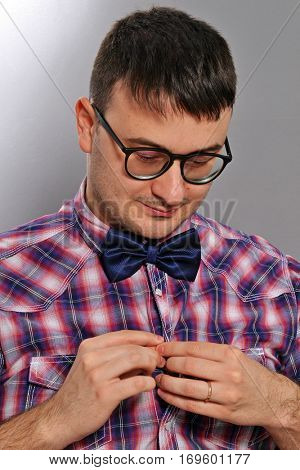 Young nerd wearing eyeglasses buttoning his shirt