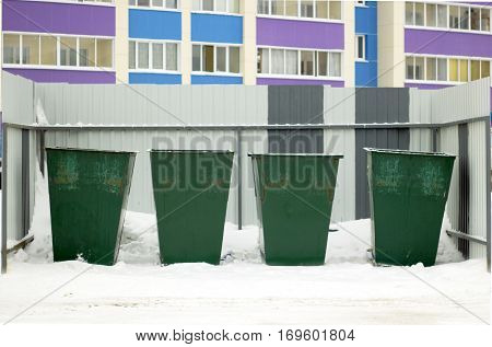 Green garbage containers in a row on the street in winter